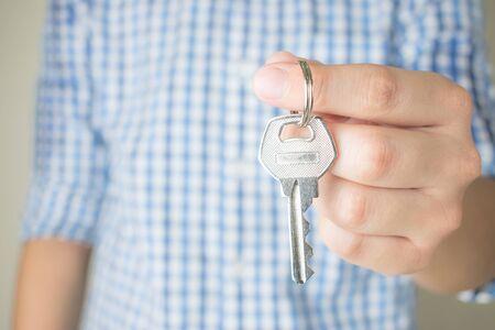 Asian people wear blue plaid shirts holding keys, close up.