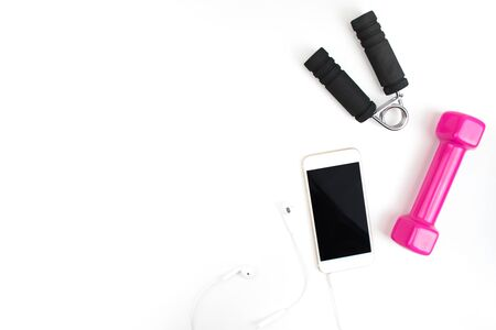 Exercise equipment with pink dumbbells, smartphones, headphones in a white background. Top view. 版權商用圖片