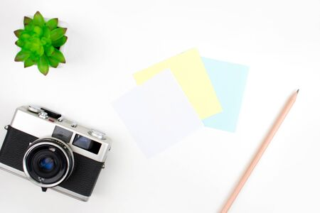 Note pad, film camera, pencils and plant pots on a white desk. Top view, Flat lay. 版權商用圖片