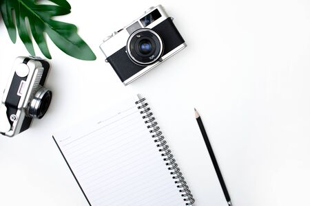 Top view of film camera with notebook, pencil and leaves. Isolated white background.