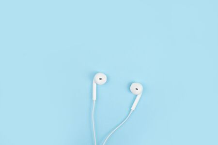 Earphone on a blue background. Close up.