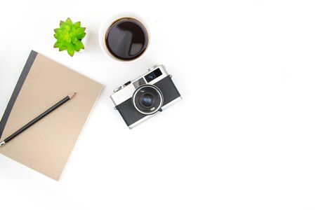 White photographer desk with film camera and notebook with copy space. Top view.