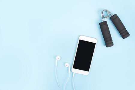 Fitness Concepts. Exercise to lose weight with a smartphone, earphone on a blue background. With copy space.