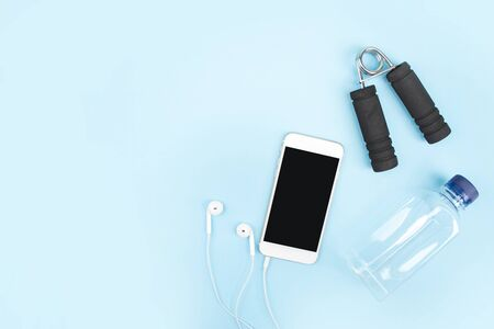 Exercise to lose weight with a smartphone, headphones and water bottles on a blue background. With copy space.