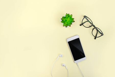 Top view with eye glasses and smartphone on a yellow background. Flat lay. 版權商用圖片