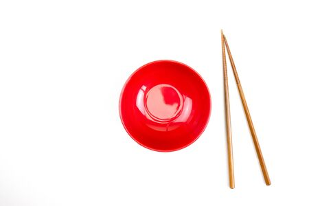 Top view of the red bowl and chopsticks on the white table background.
