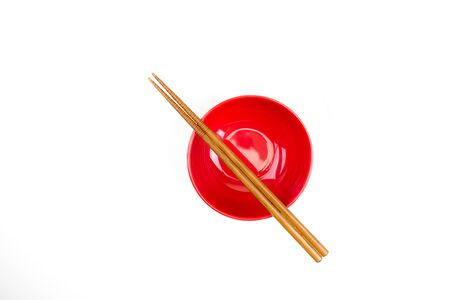 Top view of chopsticks placed on a red bowl. Isolated background.