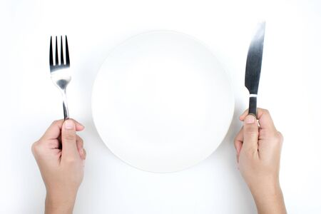 Restaurant and Food theme. A hand holding a spoon and an empty plate on a white background. 版權商用圖片