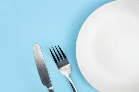 Top view of the plate and spoon on the blue background with the copy space.