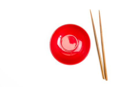 Top view of red bowl with wooden chopsticks on a white background. Isolated background.