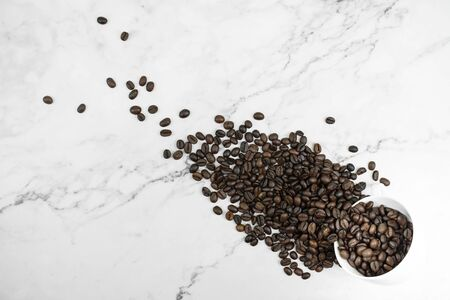 Pour a white glass with the coffee beans arranged on a marble pattern in the top view.