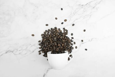 Overturned white glass and coffee beans arranged on a marble pattern in the top view. Isolated background.