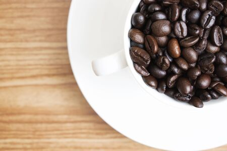 Coffee beans in a glass on a wooden background with copy space, top view.