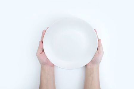 The top view of the hand is holding a white plate. 版權商用圖片