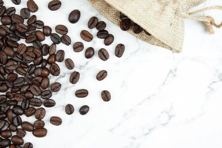 Pour brown coffee beans in a cloth bag on a marble background with copy space. Top view. Banco de Imagens
