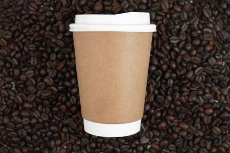 Hot coffee mug on brown coffee beans, top view.
