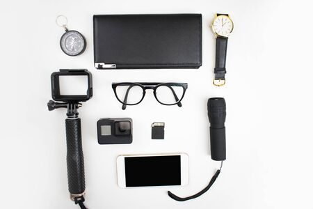 Top view of the black accessories for tourists with a camera, glasses, flashlight, compass, wallet and smartphone on a white background.