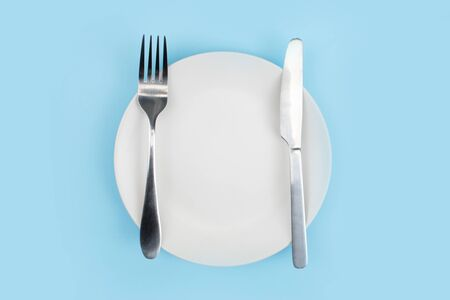 A white plate with a spoon on a blue background. Top view.