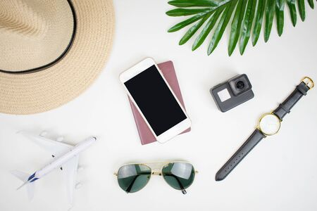 Travel accessories suitable for a young holiday with a hat, passport, smartphone, camera, watch and sunglasses in the top view.