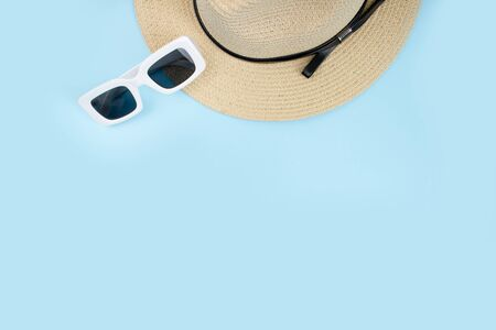 Hat with sunglasses on a blue background, top view, summer concept.