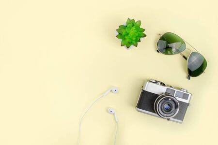 Holiday with film camera, sunglasses on a yellow background. Top view. Summer concept.