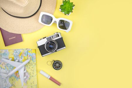 A girls vacation with a hat, map, smartphone, film camera and sunglasses on a yellow background. Top view. Summer concept.