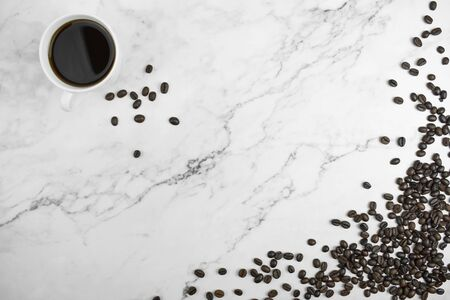 Top view of brown coffee beans with coffee on a marble background with copy space.
