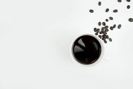 Black coffee in a white glass with coffee beans on a white background with copy space. Isolated background.