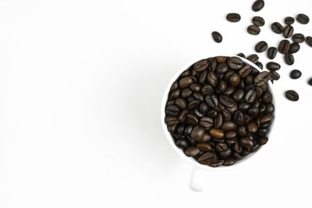 Coffee beans in a white mug on a white background with copy space. Close up.