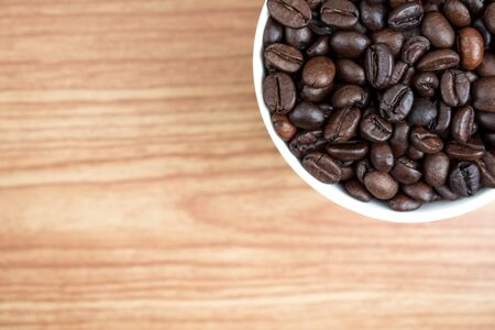 Coffee beans in a white mug on an old brown wood texture background. With copy space.