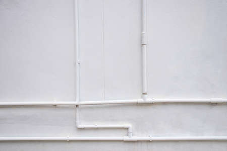 White water pipe system installed on white concrete wall. Reklamní fotografie