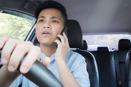 Front view of Asian people using mobile phones and having conversations while driving.
