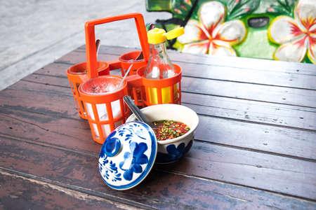 Sugar, fish sauce, vinegar, cayenne pepper, seasoning, Thai noodles on old wooden table.