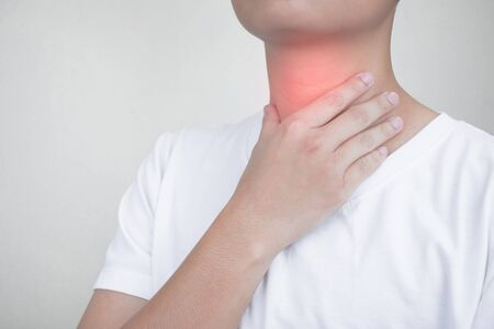 Asian people feel sore throat due to tonsillitis using their hands to touch the neck. Isolated background.