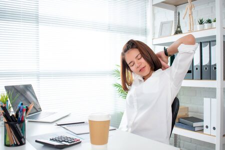 Asian businesswoman wears a white shirt stretching back and feels relaxed at the desk.