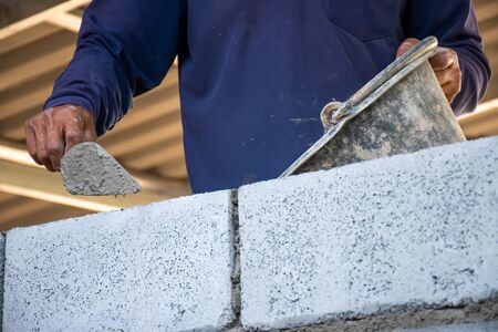 Close-up of hands construction workers are using bricks and mortar for building walls in construction sites. Stock Photo