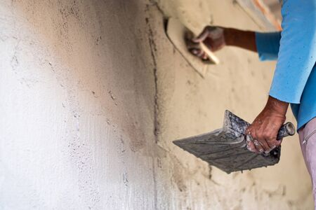 Construction workers are plastering the cement for building walls with plastering tools.