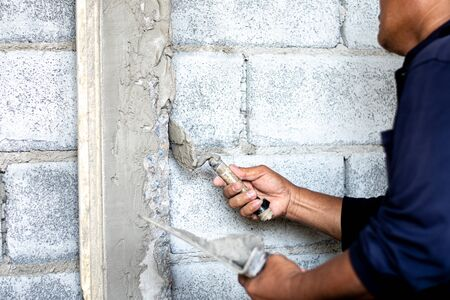 Construction workers use cement plaster to build house posts. Stockfoto