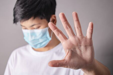 Stop viruses and pestilence. A close up of a healthy young Asian man wearing a protective mask and showing a stop gesture