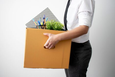 The side view. The employee was fired from carrying a brown cardboard box with his equipment. On a white background.