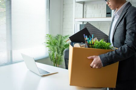 Young businessmen wear gray suits, feel stressed and are packing items into cardboard boxes. Unemployment and business concepts