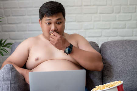 Fat man is shocked while watching a movie on a laptop with popcorn at home.
