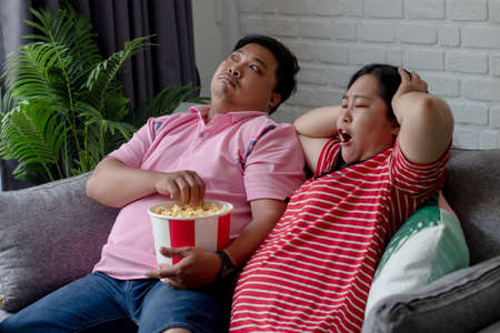 Portraits of young couple shocking and eating popcorn sitting on the sofa watching TV at home.