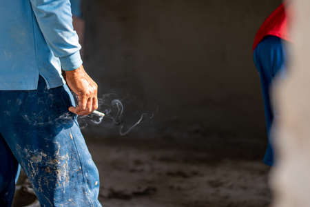 Workers smoke on the construction site. Health care concept.