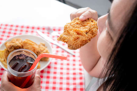 Woman eating fried chicken with a glass of soft drink.