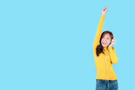 Beautiful Asian women are happy wearing headphone listening to music and dancing on a light blue background.