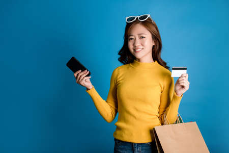 Beautiful Asian woman smiling, carrying shopping bags and showing credit cards in the studio.