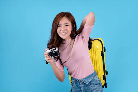 Beautiful Asian woman is excited and carrying a suitcase ready to travel.