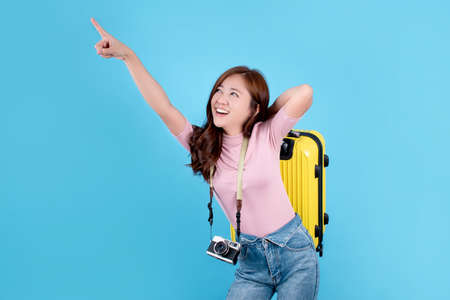 Beautiful Asian woman is smiling, carrying a yellow suitcase and pointing to an empty space by hand on a blue background. Reklamní fotografie
