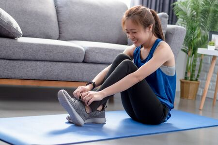 Smiling young Asian woman are exercising at home. She tied the shoe cord. Фото со стока